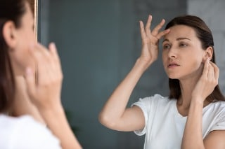 Woman looking at wrinkles in the mirror