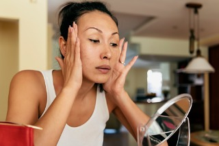 Woman tightens her skin in the mirror