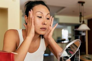 Woman tightening her skin in the mirror